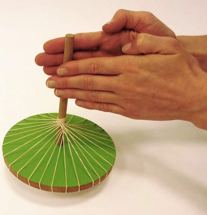זוג ידיים מסובבות סביבון חוטים ירוק בסדנת העיצוב בחולון