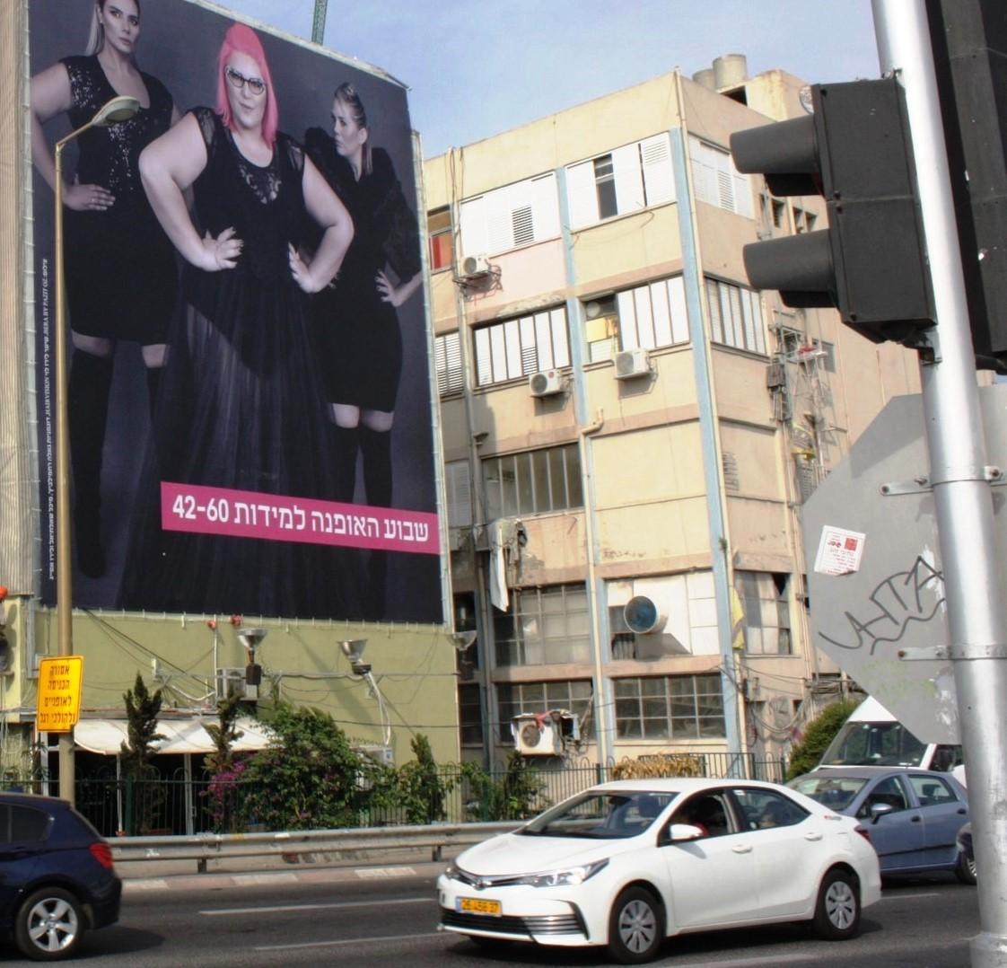 מודעת שבוע האופנה למידות גדולות (42-60) עם גאלה רחמילביץ במרכזה, על בניין באיילון
