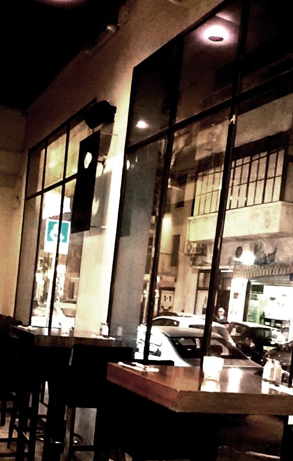 הבתים המתקלפים של תל אביב הקטנה מפעם, נשקפים דרך כתלי הזכוכית של המסעדה